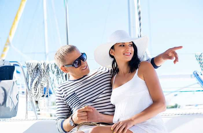 a man and a beautiful woman on a yacht